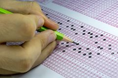 Students taking exams, writing examination room with holding pencil on optical form of standardized test with answers paper.  stock photos
