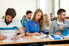 Students taking notes in a classroom. Young students taking notes in a classroom Royalty Free Stock Photo