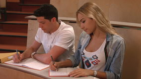 Students taking notes in lecture stock footage