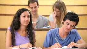 Students taking notes while their classmates are chatting Stock Photos