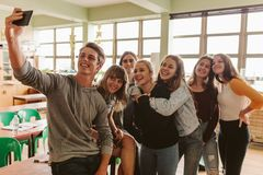 Students taking selfie in classroom. Group of university students making a selfie with smart phone in classroom. Young people in lecture room taking selfie with royalty free stock photography