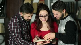 Students talking together in the library with book. Students talking together about book in the library and searching for information. Young girl in eyeglasses stock footage