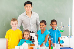 Students teacher chemistry. Smiling elementary school students and teacher in chemistry class royalty free stock photos