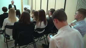 Student writing the text for work using the smartphone indoors in the audience. View from behind of a group of students. Students with teacher in classroom stock video footage