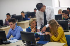 Students with teacher  in computer lab classrom Stock Photo