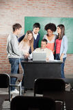 Students And Teacher Discussing Over Laptop In. Group of students and teacher discussing over laptop at desk in classroom Royalty Free Stock Images