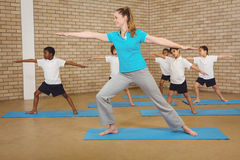 Students and teacher doing yoga pose. At elementary school Royalty Free Stock Photo