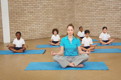 Students and teacher doing yoga pose. At the elementary school Royalty Free Stock Images