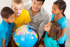 Students teacher globe. Group of adorable students with teacher looking at the globe Royalty Free Stock Photos