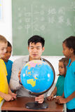 Students teacher globe. Group elementary school students and teacher looking at globe in classroom Royalty Free Stock Images