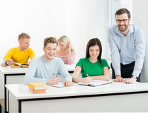 Students and the teacher learning in a classroom.  Stock Photos