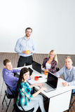 Students with teacher studying using modern technologies. Young startupers have a meeting with a boss Stock Photography