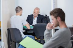 Students and teacher with test results in classroom stock images