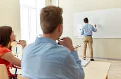 Students and teacher writing on school white board Royalty Free Stock Photography
