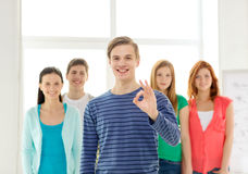 Students with teenager in front showing ok sign Stock Photo
