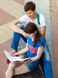 Students or teenagers with notebooks outdoors Stock Images