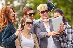 Students or teenagers with tablet pc taking selfie Royalty Free Stock Image