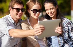 Students or teenagers with tablet pc taking selfie Stock Image