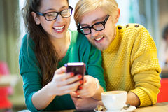 Students text messaging. Couple seated at cafe table Royalty Free Stock Photo