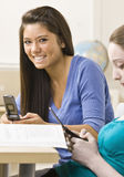 Students text messaging on cell phones Royalty Free Stock Photo