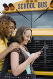 Students Text Messaging By School Bus Royalty Free Stock Images