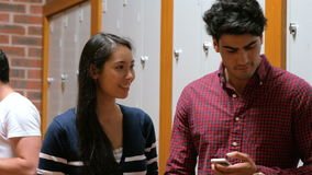 Students on their smartphone leaning on lockers. In college stock footage