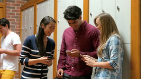 Students on their smartphone leaning on lockers. In college stock video footage