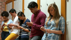 Students on their smartphone leaning on lockers