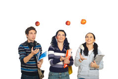 Students throw up apples. Three cheerful students throw up apples and having fun isolated on white background Stock Photo