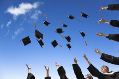 Students throwing graduation hats. In the air celebrating with blue sky Royalty Free Stock Image