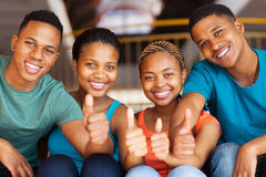 Students thumbs up. Group of cheerful students wit thumbs up royalty free stock photography