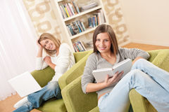 Students - Two female teenager in living room. Students - Two female teenager studying with laptop and book in modern living room Stock Images