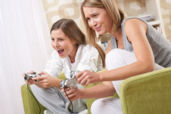 Students - Two female teenager playing TV game Royalty Free Stock Photos