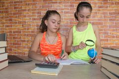 Students, two Young Girls working on his homework. Two Girls with lots of books studying for exams royalty free stock image