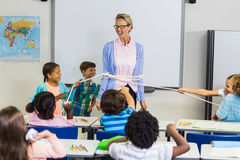 Students tying up a teacher with rope in classroom Royalty Free Stock Image