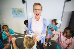 Students tying up a teacher with rope in classroom. At elementary school Stock Photos