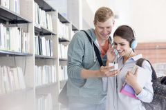 Man assisting friend in listening music through at university library royalty free stock photos