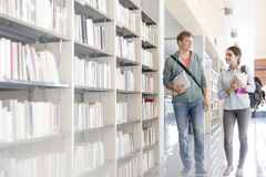 Students talking while walking by bookshelf at university library stock photography