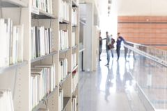 Various books arranged on shelf at corridor in university library royalty free stock photography