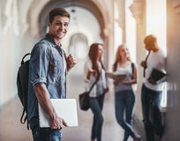 Students in university. Multiracial students are standing in university hall during break. Handsome young men with laptop in hand is on the foreground Royalty Free Stock Photography