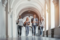 Students in university. Multiracial students are walking in university hall during break royalty free stock photos