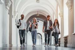 Students in university. Multiracial students are walking in university hall during break and communicating Royalty Free Stock Image