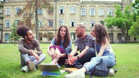 Students in university park sitting on lawn.