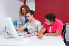Students using computer together and taking notes. At the college Stock Image