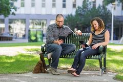 Students Using Digital Tablet On Bench At Campus. Male and female university students using digital tablets on bench at campus Royalty Free Stock Photos