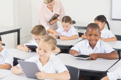 Students using digital tablet in classroom. At school Royalty Free Stock Photos