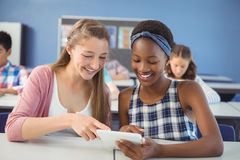 Students using digital tablet in classroom. At school Stock Photography