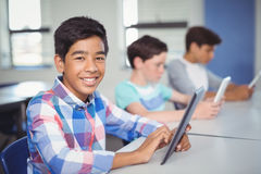 Students using digital tablet in classroom. At school Royalty Free Stock Images