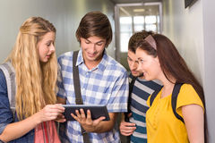 Students using digital tablet at college corridor. Portrait of happy students using digital tablet at college corridor Stock Image