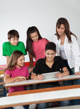 Students Using Digital Tablet At Desk. High school students using digital tablet at desk in classroom Royalty Free Stock Image